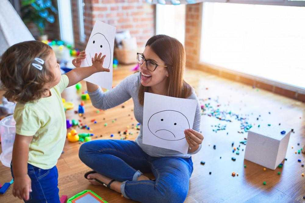 a teacher holds up two drawings of a smile and a sad face in front of a child, who is grabbing the happy face paper