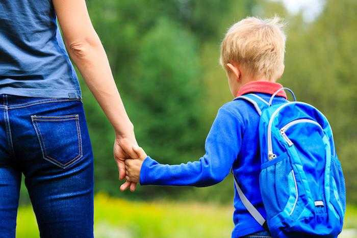 a young boy holds the hand of an adult with his backpack on