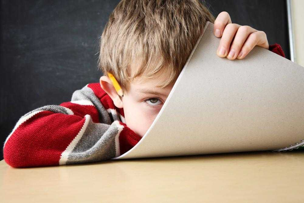 child with a pencil in his ear hiding behind a notebook