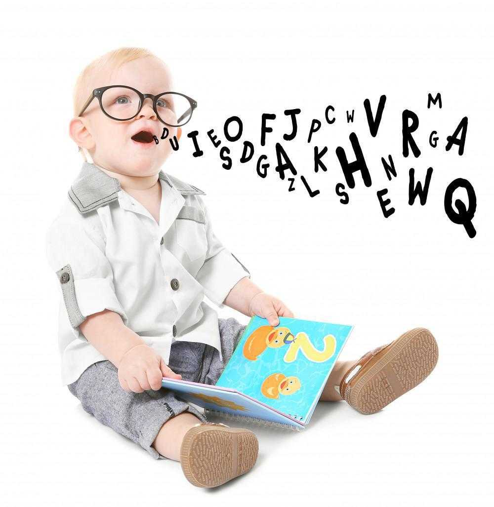 baby with glasses reading a book and letters are coming out of his mouth, representative of speech therapy and learning the alphabet