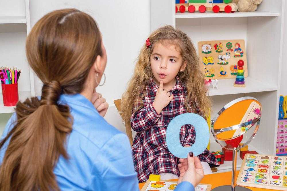 a woman and a young child point to their chins as the young girl learns the letter O that the teacher holds up