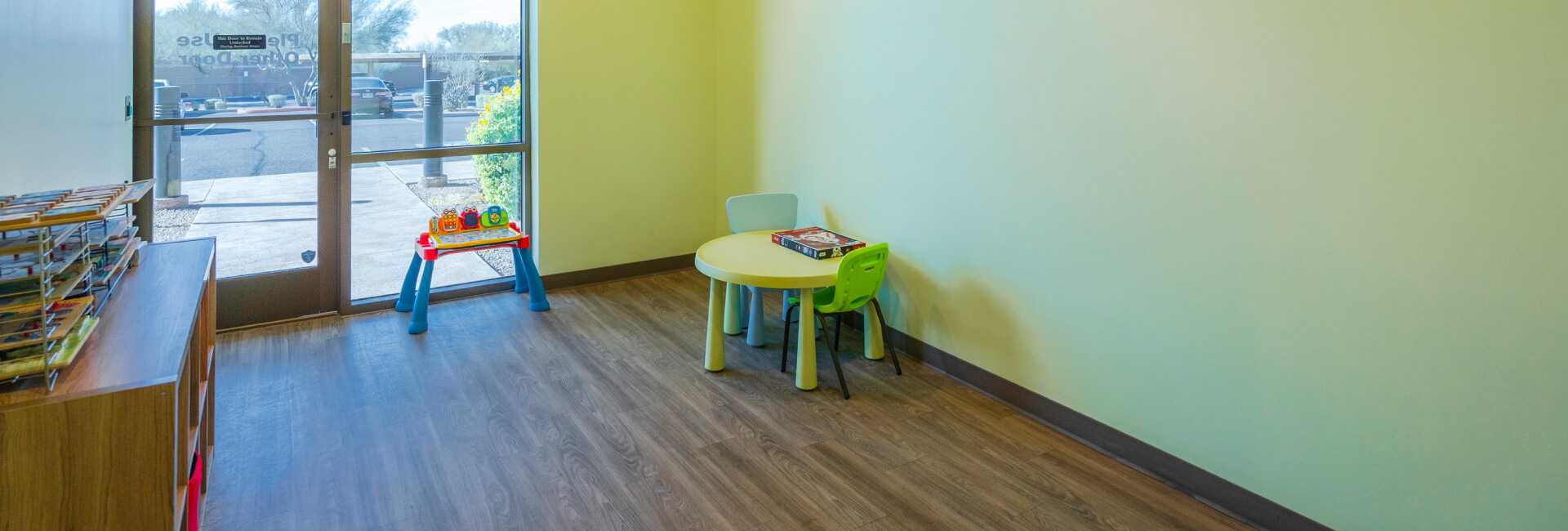 a room inside the Scottsdale Children's Institute with a bookshelf and table in the corner