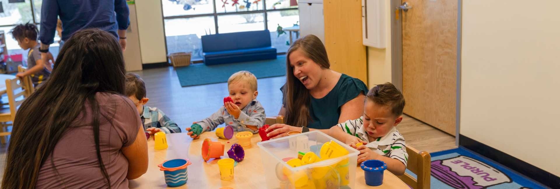 two teachers play with children at a table with toys