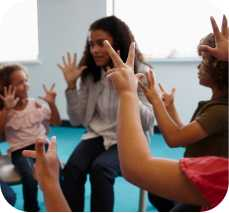 a teacher and children hold up their hands signaling numbers