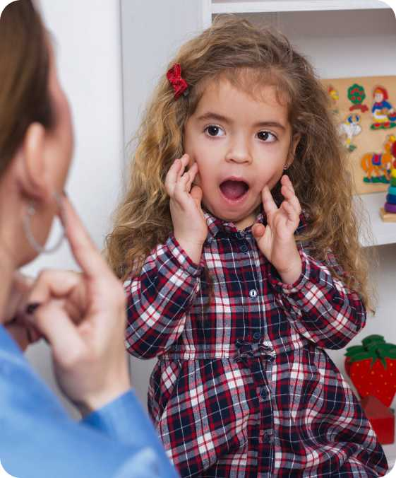 a young girl makes a face with her mouth open and her hands to her cheeks while a teacher mirrors her reaction, image indicative of speech therapy