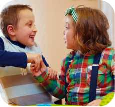 two children shake hands and smile at each other