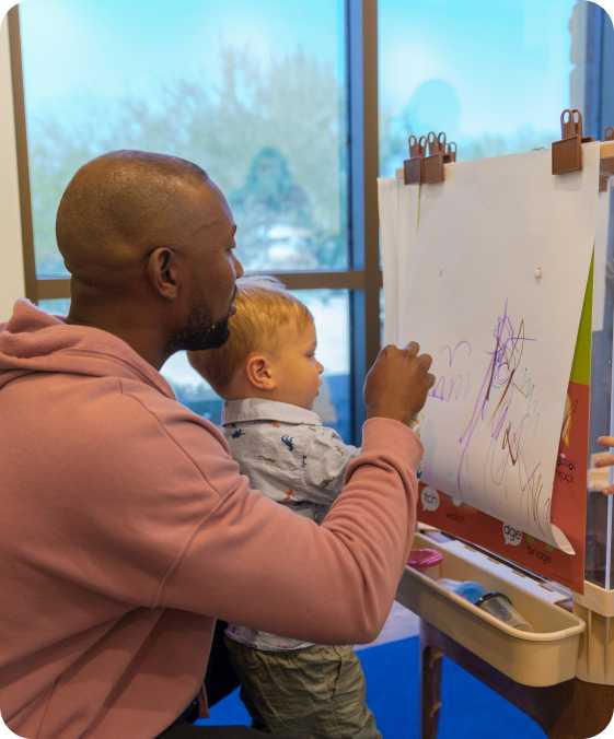 a man and a child draw on a piece of paper on an easel