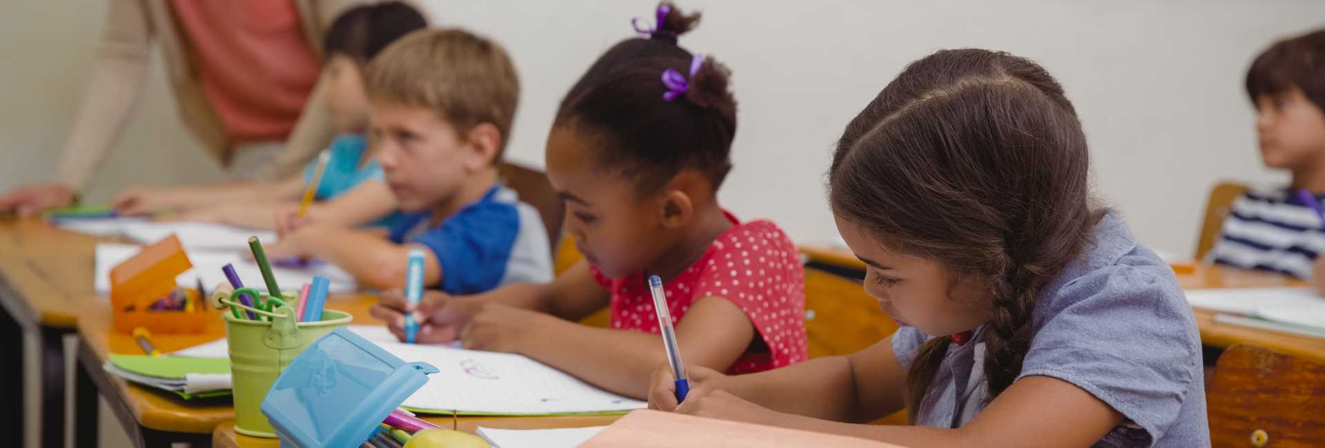 a group of children writing at a desk