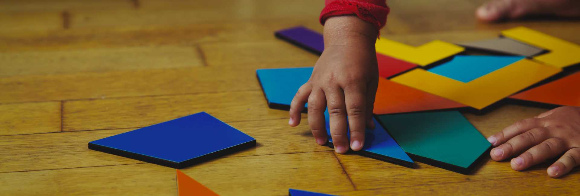 a child's hand reached for building toys on the floor