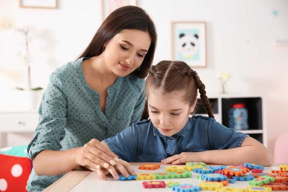 a female teacher and a young girl play with puzzle toys at a table