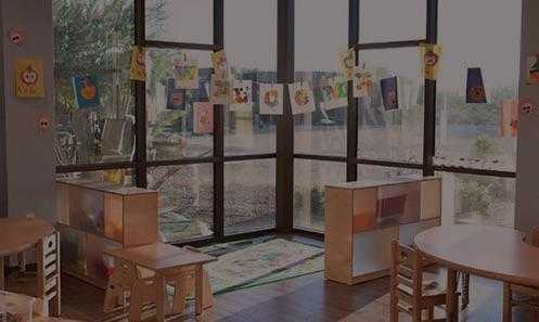 a room with bright windows and children's art on the window, surrounded by kids tables and chairs