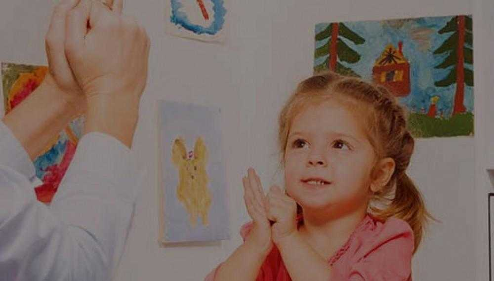 a young girl hand signs to a person off camera