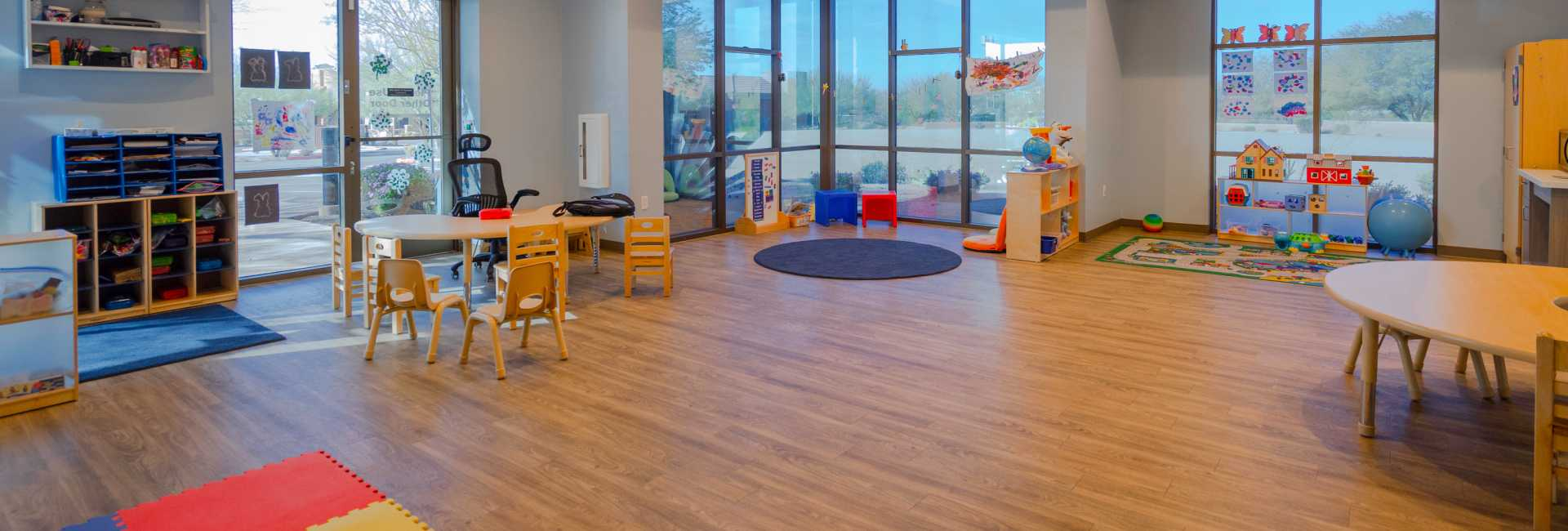 a wideshot of the playroom in the Scottsdale Children's Institute featuring tables, chairs, and toys