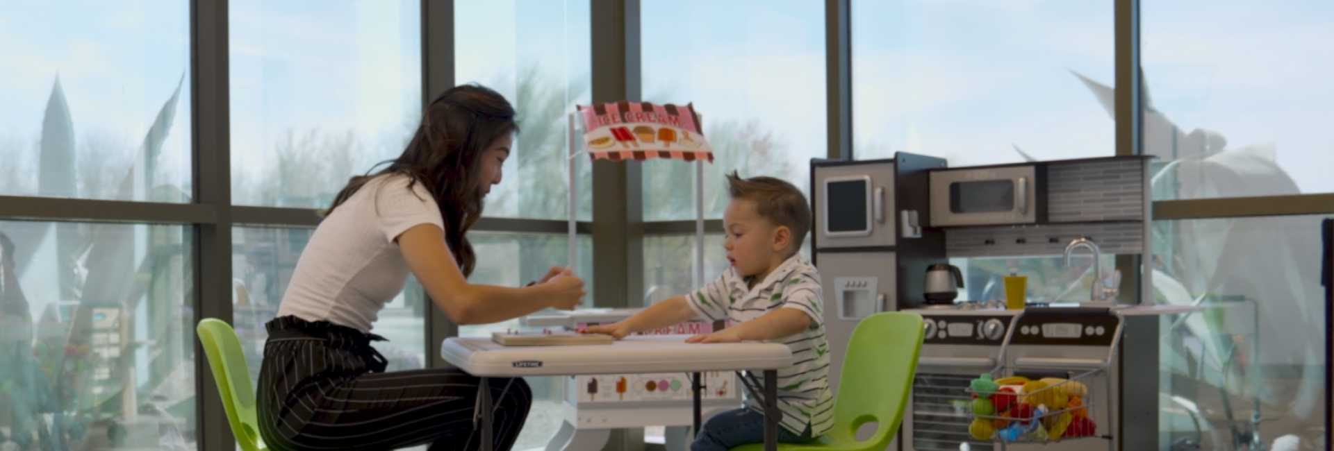 a woman and a child at a desk learning