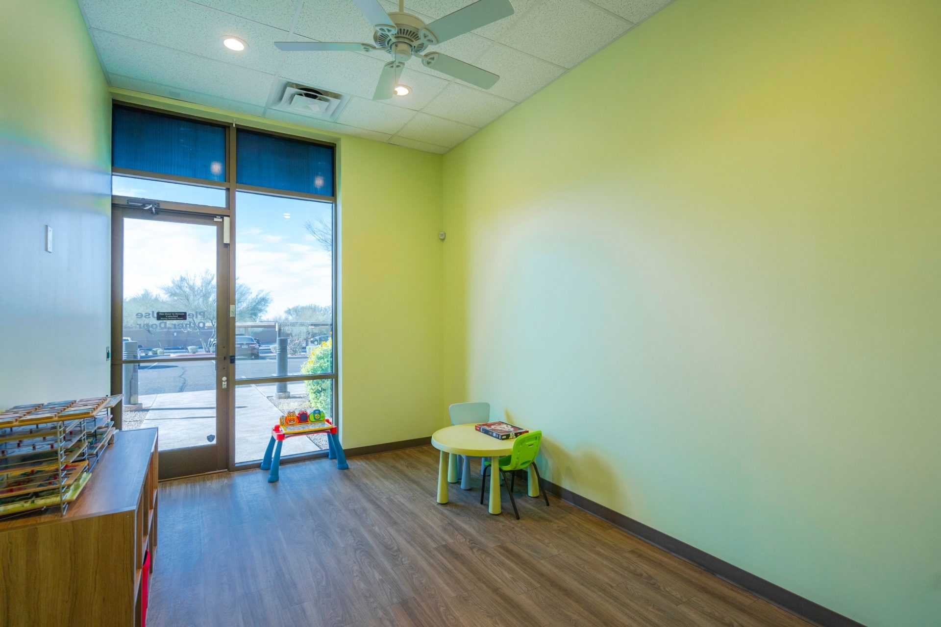 a play and toy room in the Scottsdale Children's Institute with a table in the corner