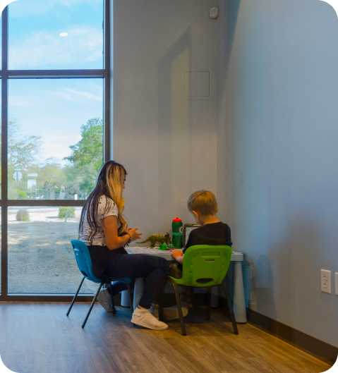a woman and a child sitting at a desk in the Scottsdale Children's Institute