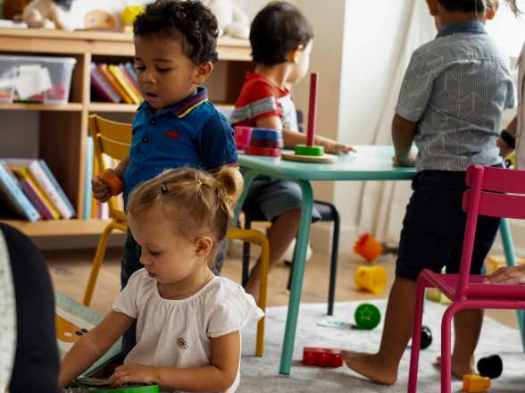 children play with toys at tables
